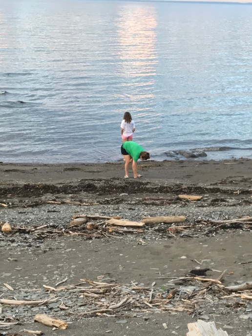 Maddie, in foreground, picks up sea glass. While Gracie, in the background, looks towards the Bay of Choler.