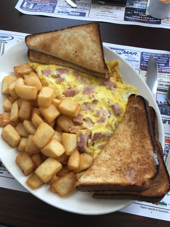 John ordered a delicious ham and cheese omelet served with potatoes, toast, and of course, plenty of coffee!