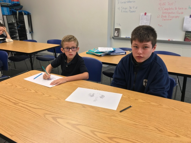 Oakley Mullins, 3rd grade, teaches Carson Patrick, 8th grade, how to draw a peacock.